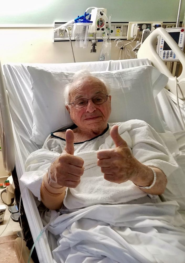 old man laying in a hospital bed giving two thumbs up