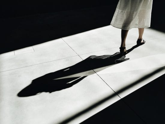 woman standing in shadows